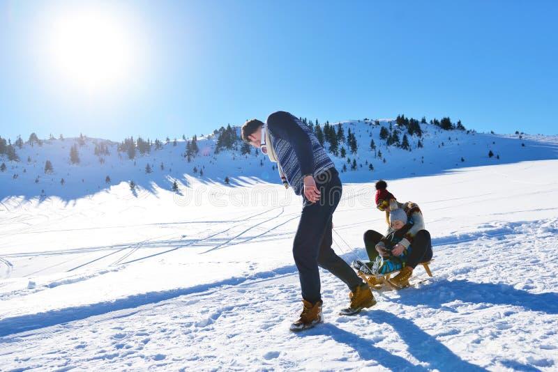 Familia joven feliz que juega en nieve fresca en el día de invierno soleado hermoso al aire libre en naturaleza imágenes de archivo libres de regalías