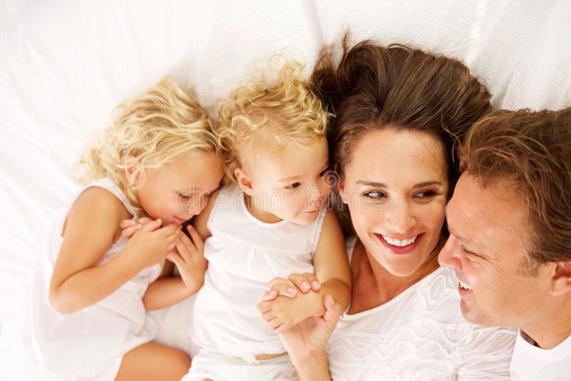 Familia joven feliz que miente junto en cama foto de archivo libre de regalías