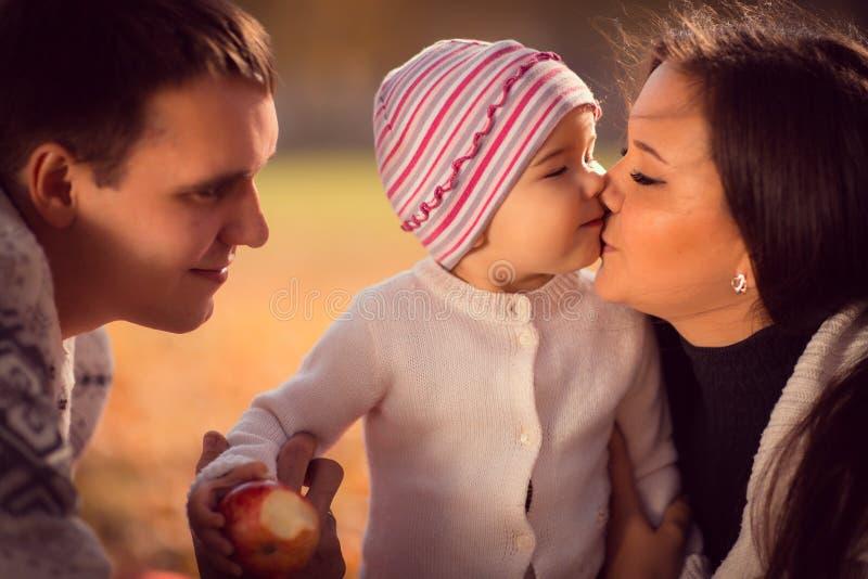 Familia joven feliz que pasa el tiempo al aire libre en el parque del otoño foto de archivo libre de regalías
