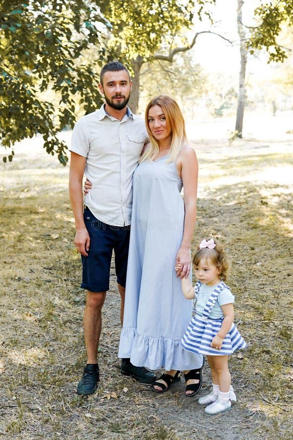 Familia joven feliz que pasa el tiempo junto afuera en naturaleza verde Padres, niñez, niño, cuidado, hija, padre, madre imagenes de archivo