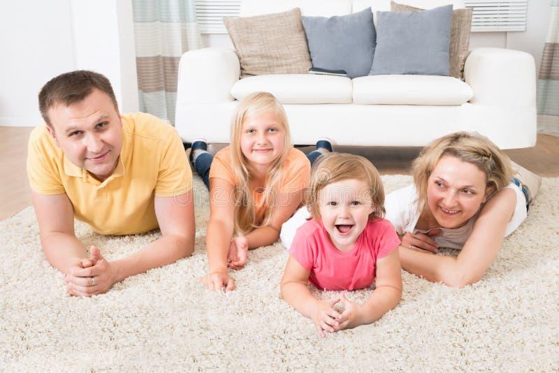 Familia joven feliz que pone en la alfombra imágenes de archivo libres de regalías