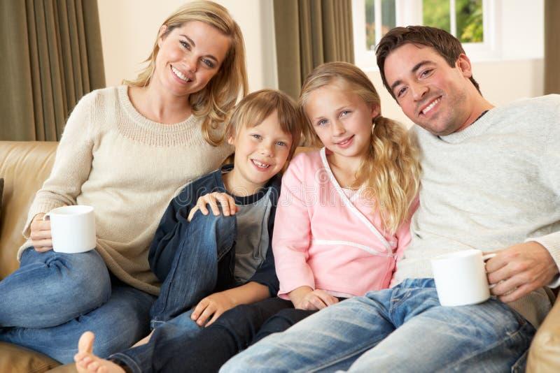 Familia joven feliz que se sienta en las tazas de la explotación agrícola del sofá