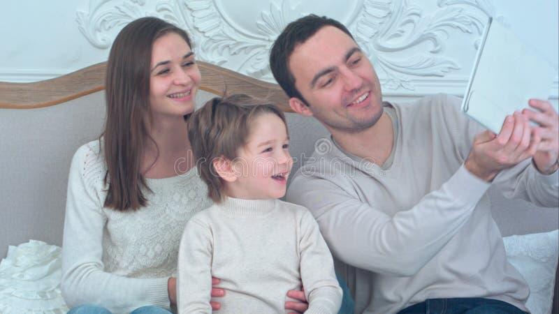 Familia joven feliz que toma selfies en el sofá con la tableta imagenes de archivo