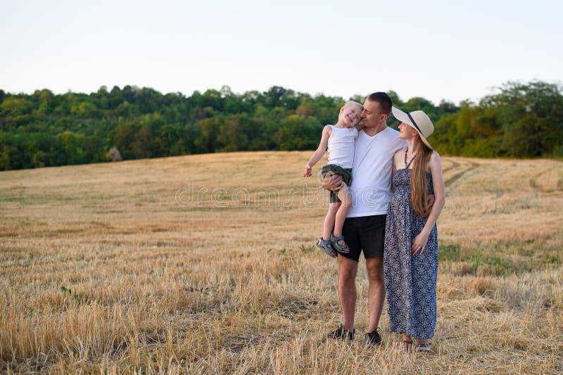 Familia joven feliz Un padre con un peque?o hijo en sus brazos y una madre embarazada Campo de trigo biselado en el fondo Puesta  fotos de archivo libres de regalías