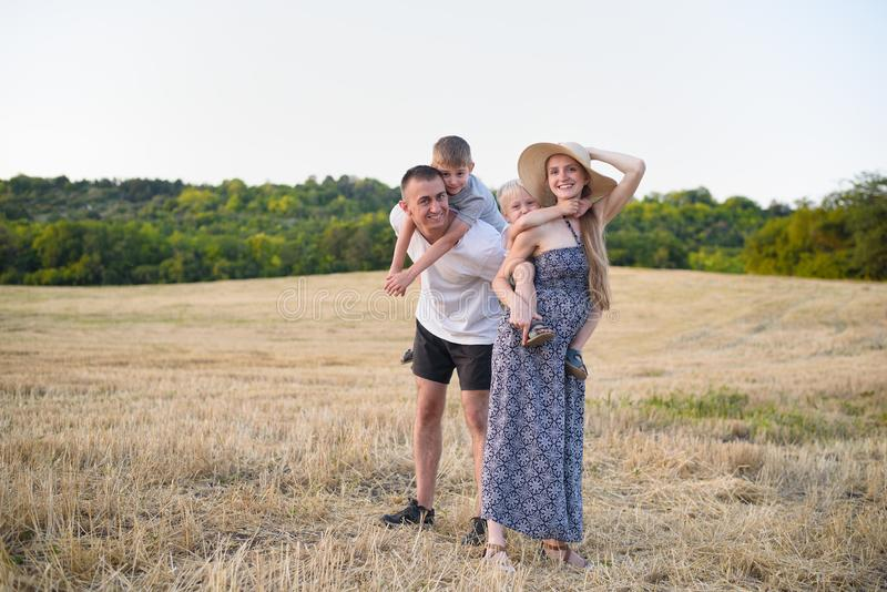 Familia joven feliz Un padre, una madre embarazada, y dos pocos hijos en sus partes posteriores Campo de trigo biselado en el fon imágenes de archivo libres de regalías