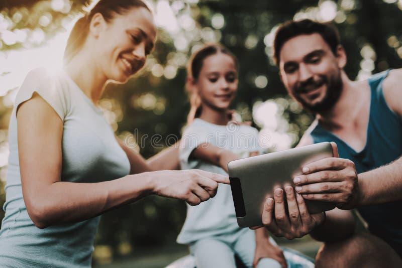 Familia joven feliz usando la tableta en parque del verano foto de archivo