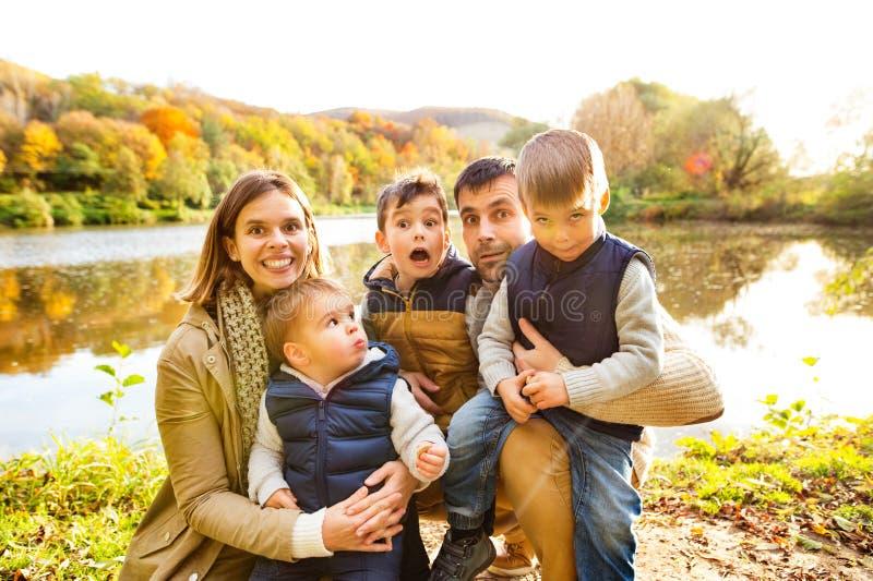 Familia joven hermosa en un paseo en bosque del otoño imagenes de archivo