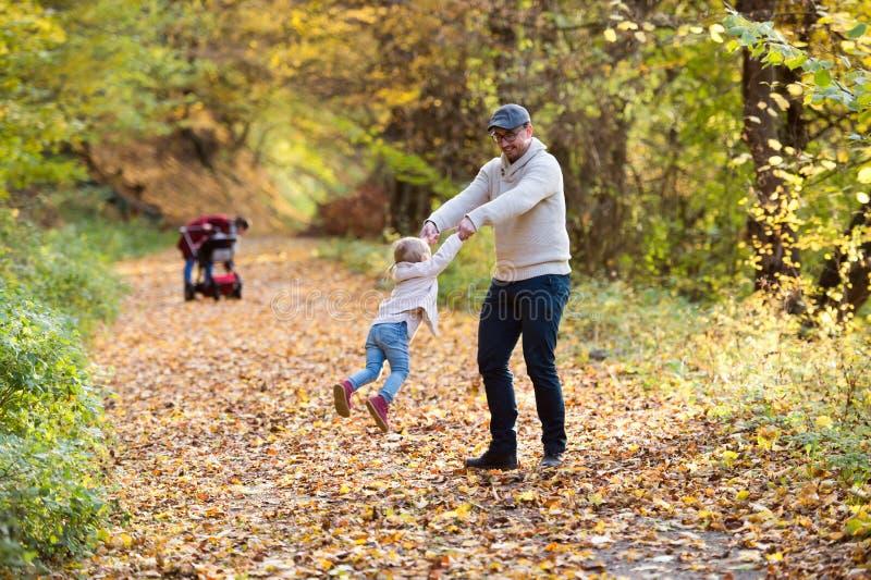 Familia joven hermosa en un paseo en bosque del otoño imágenes de archivo libres de regalías