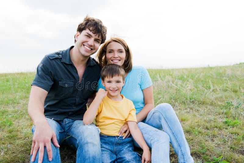 Familia joven hermosa feliz que presenta al aire libre fotografía de archivo libre de regalías