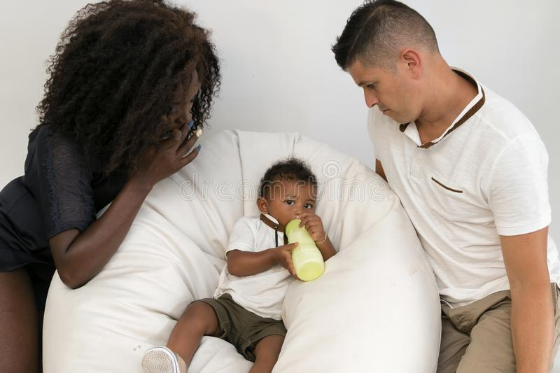 Familia joven Padres que alimentan a un niño infantil con leche Multi y imagenes de archivo