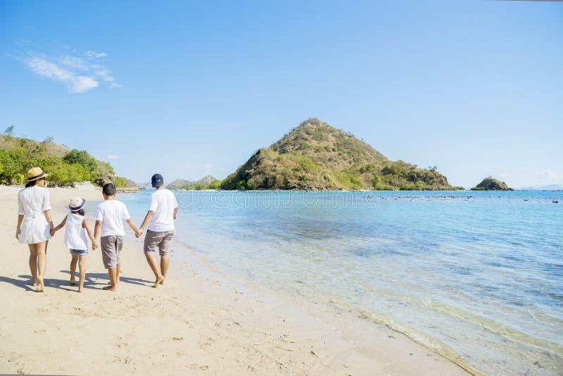 Familia joven que camina en la playa tropical imagenes de archivo