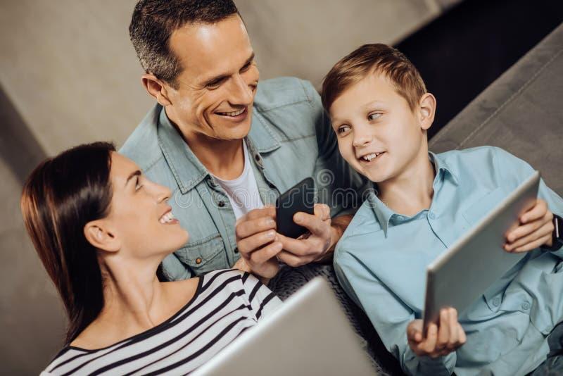 Familia joven que charla mientras que usa sus artilugios imágenes de archivo libres de regalías
