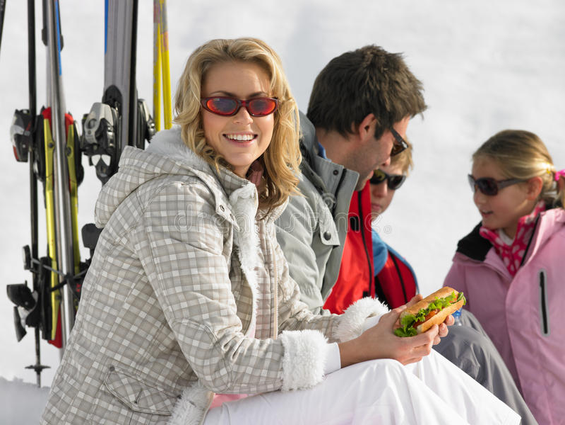 Familia joven que comparte una comida campestre el vacaciones del esquí imagenes de archivo