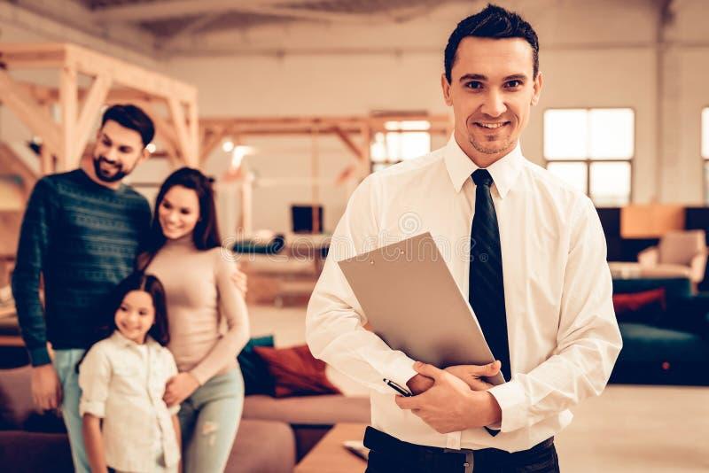 Familia joven que consulta con el vendedor de los muebles fotografía de archivo