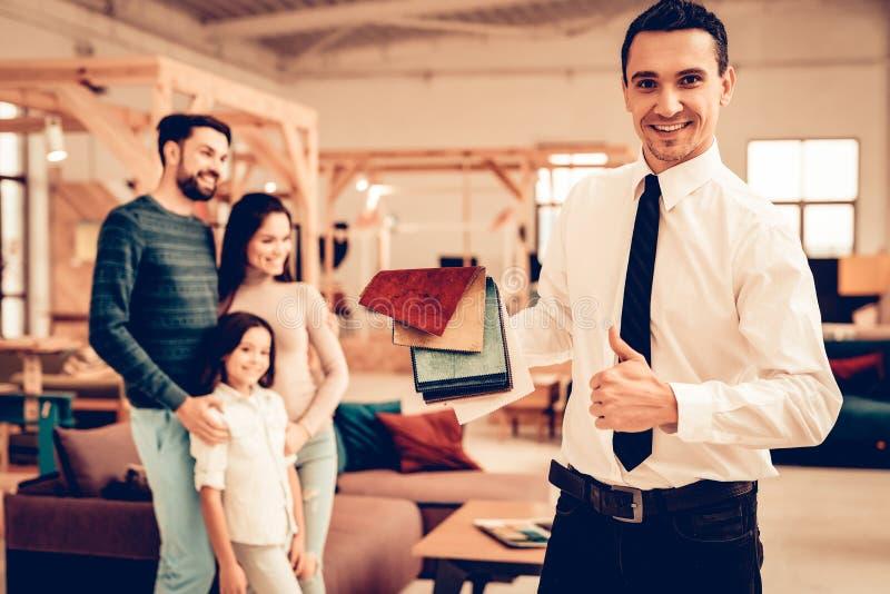 Familia joven que consulta con el vendedor de los muebles imagen de archivo