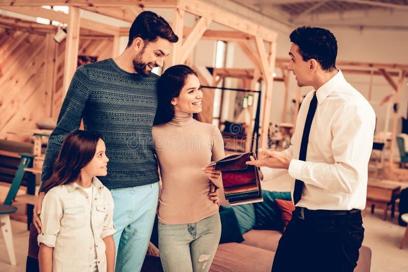 Familia joven que consulta con el vendedor de los muebles fotografía de archivo libre de regalías