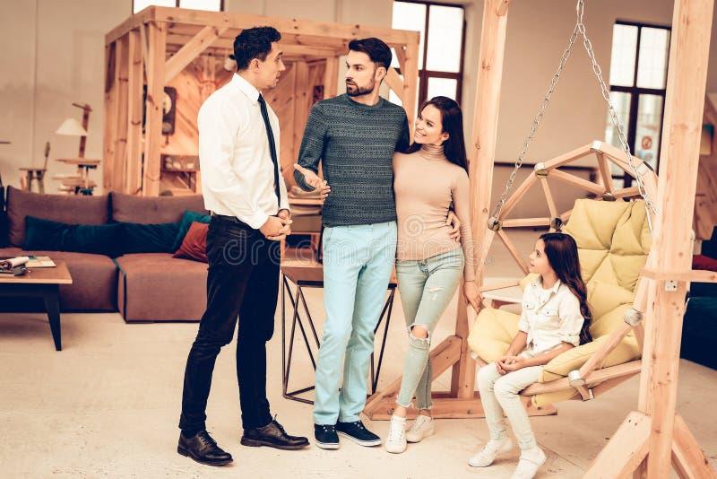 Familia joven que consulta con el vendedor de los muebles imagen de archivo libre de regalías