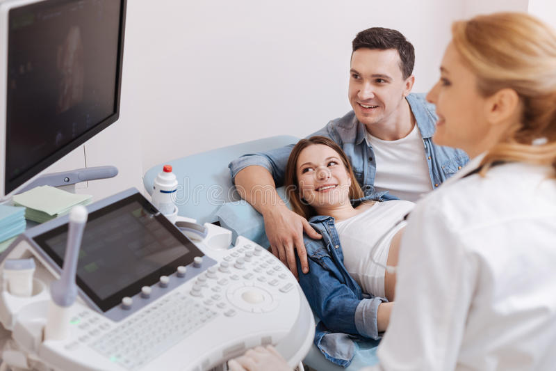 Familia joven que disfruta de la cita en el gabinete de la sonografía imagen de archivo