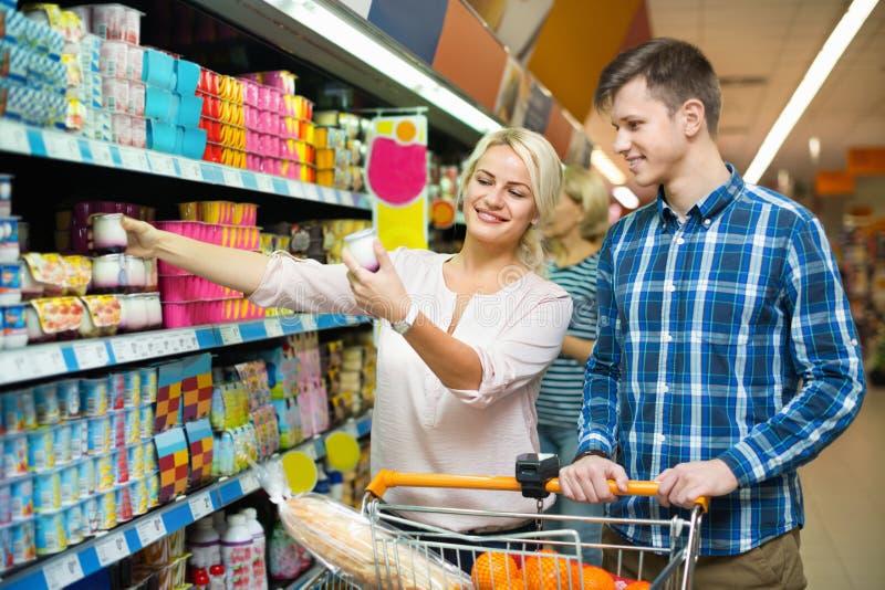 Familia joven que elige los productos lácteos y la sonrisa imagenes de archivo