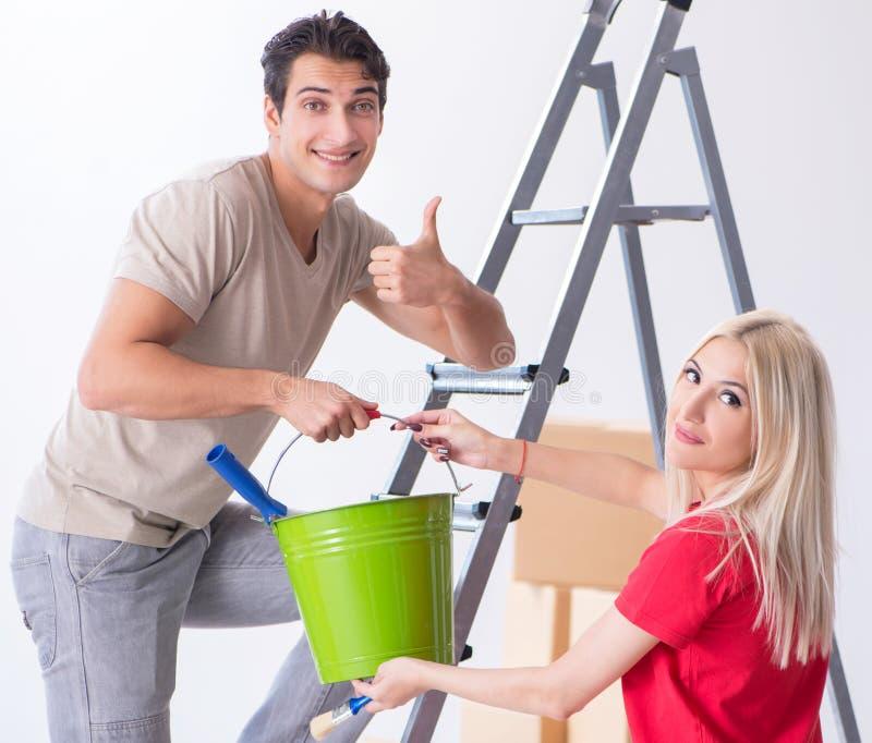 Familia joven que hace trabajo de la pintura durante la renovaci?n casera fotos de archivo libres de regalías