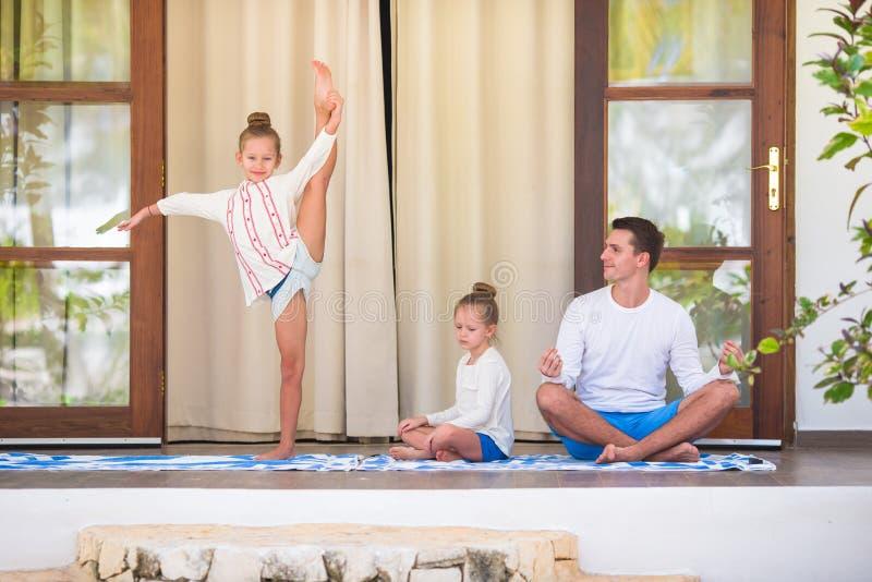 Familia joven que hace yoga y que reflexiona sobre la terraza foto de archivo