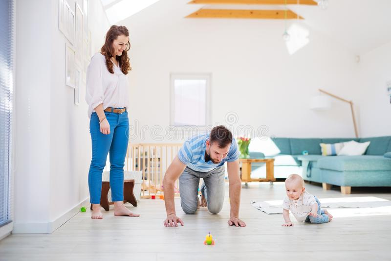 Familia joven que juega con un bebé en casa fotografía de archivo