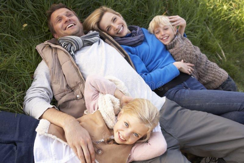Familia joven que miente junto en hierba foto de archivo