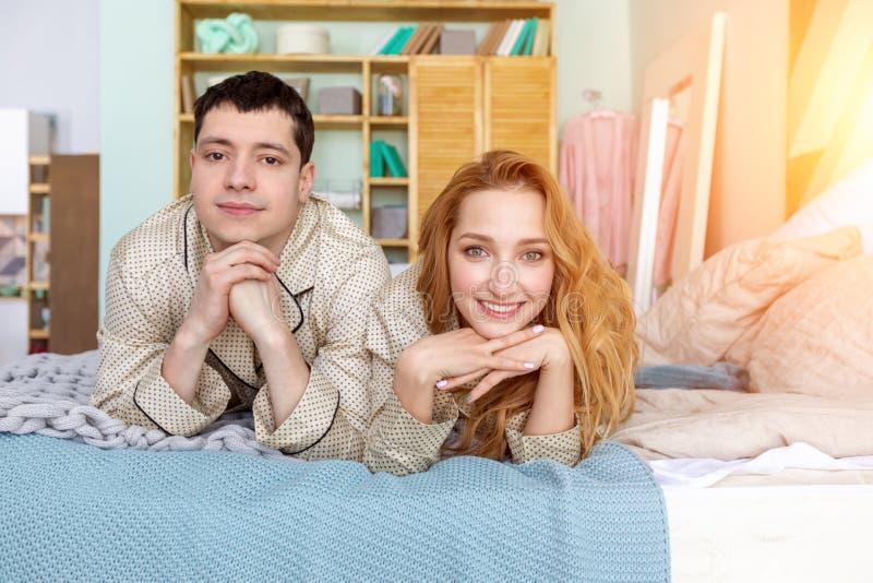 Familia joven que presenta en la cama imagenes de archivo