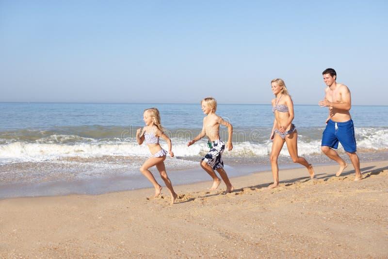 Familia joven que se ejecuta en la playa imagen de archivo libre de regalías