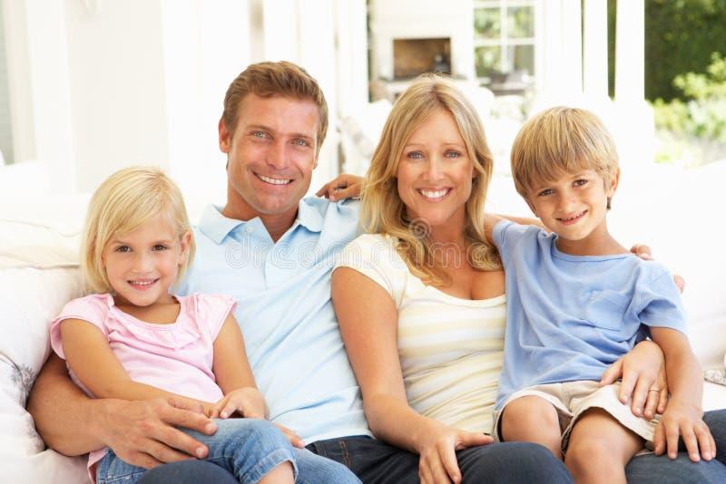 Familia joven que se relaja junto en el sofá imágenes de archivo libres de regalías