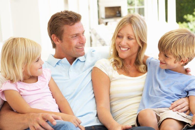 Familia joven que se relaja junto en el sofá fotos de archivo