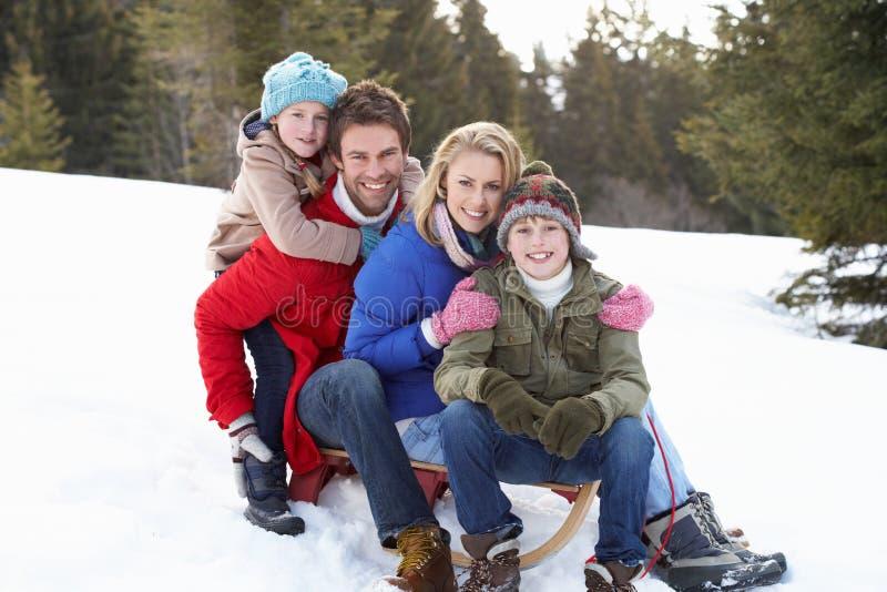 Familia joven que se sienta en un trineo en la nieve foto de archivo