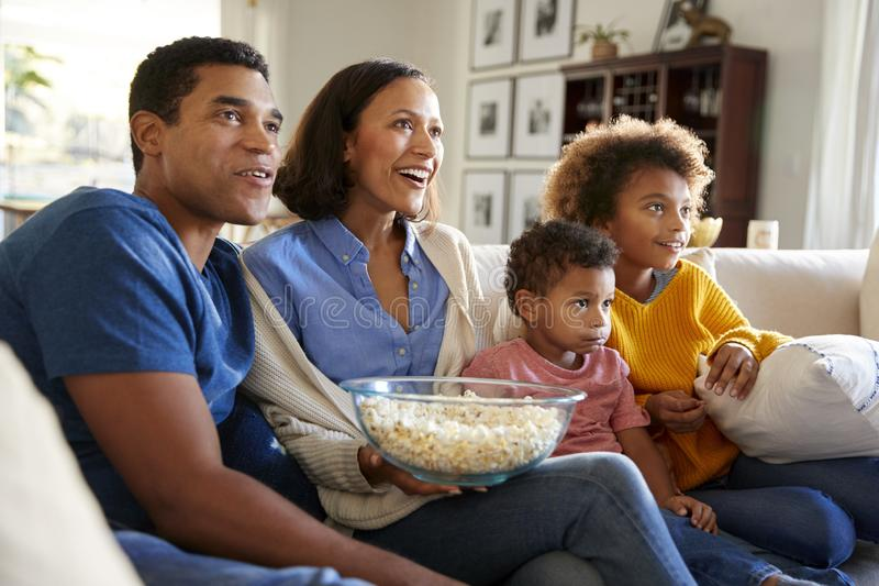 Familia joven que se sienta junto en el sofá en su sala de estar que ve la TV y que come las palomitas, vista lateral imagen de archivo