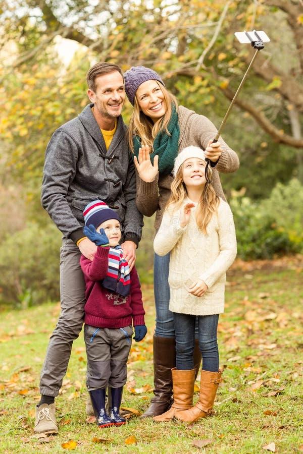 Familia joven sonriente que toma selfies imagenes de archivo