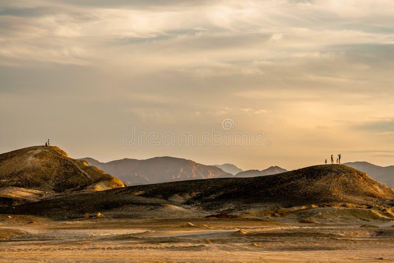Familia joven y pares jovenes del amor en el desierto egipcio en la puesta del sol fotografía de archivo