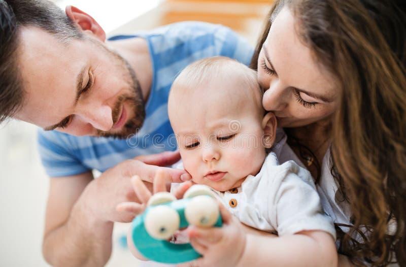 Familia joven y un bebé con un juguete en casa Cierre para arriba foto de archivo libre de regalías