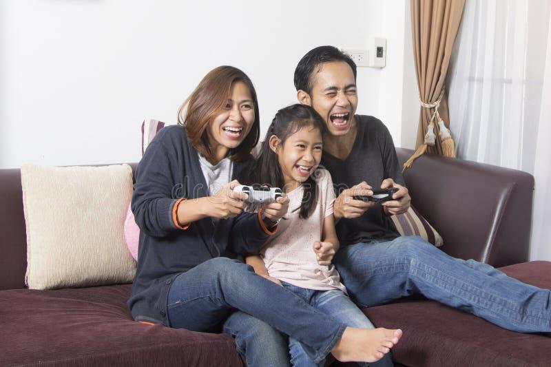 Familia juguetona que juega a los videojuegos imagenes de archivo