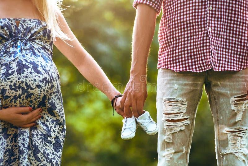 Familia juntos que sostiene los zapatos de bebé en manos y situación que el verano parquea La mujer está embarazada fotos de archivo libres de regalías