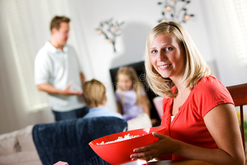 Familia: La mujer feliz sostiene el cuenco grande de palomitas antes de noche de película fotografía de archivo libre de regalías