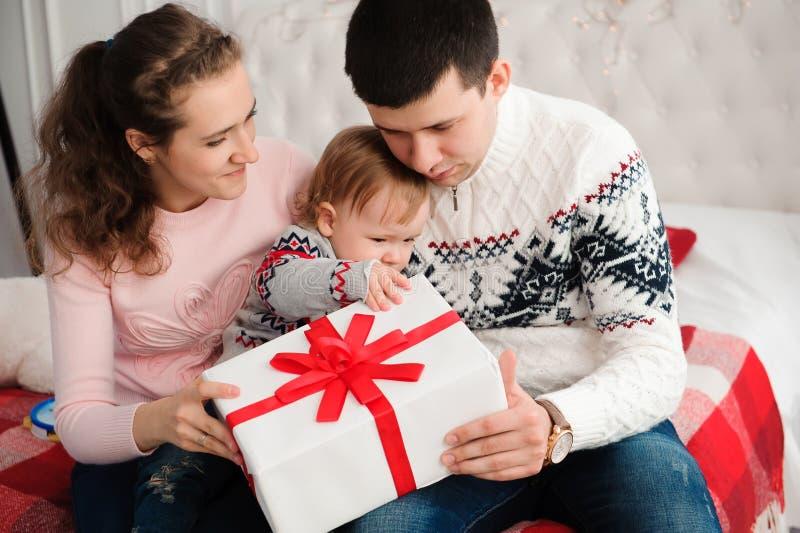 Familia, la Navidad, Navidad, invierno, felicidad y concepto de la gente - caja de regalo feliz de la abertura de la familia imagen de archivo