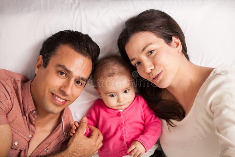 Familia latina hermosa que miente en una cama foto de archivo