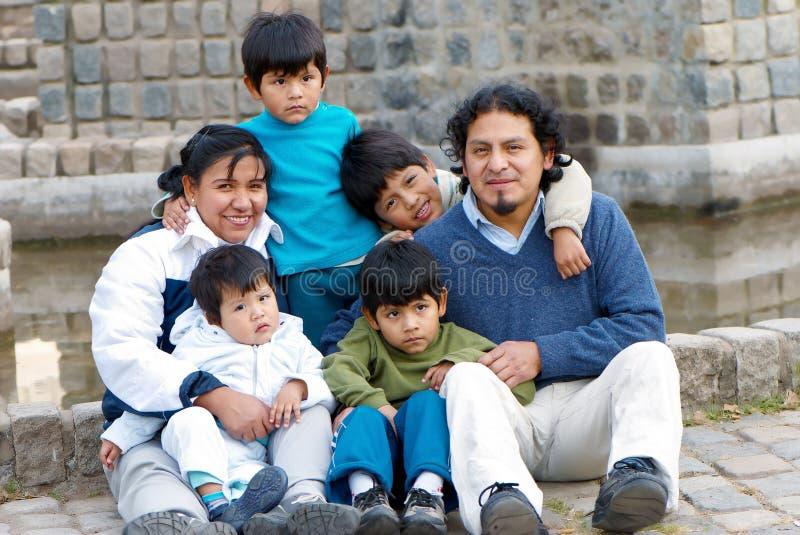 Familia latina que se sienta en la calle foto de archivo libre de regalías