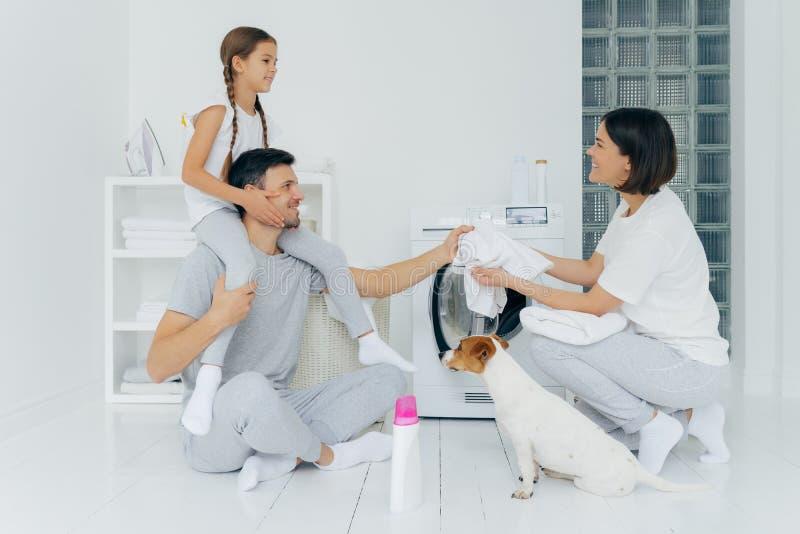 Familia, limpieza, concepto de lavado Un padre sonriente da un paseo en piggyback a una pequeña hija le da a su esposa una camise imagenes de archivo