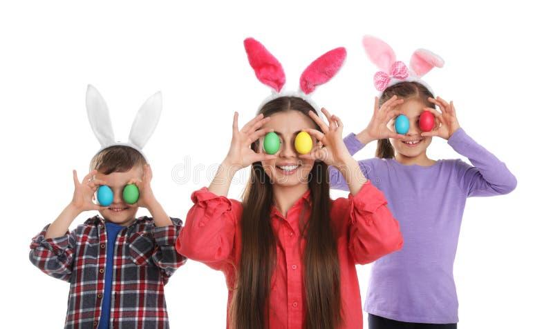 Familia linda en vendas de los oídos del conejito con los huevos de Pascua cerca de ojos en blanco foto de archivo libre de regalías