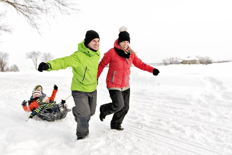 Familia linda que tira del trineo con el paisaje Nevado imagen de archivo libre de regalías