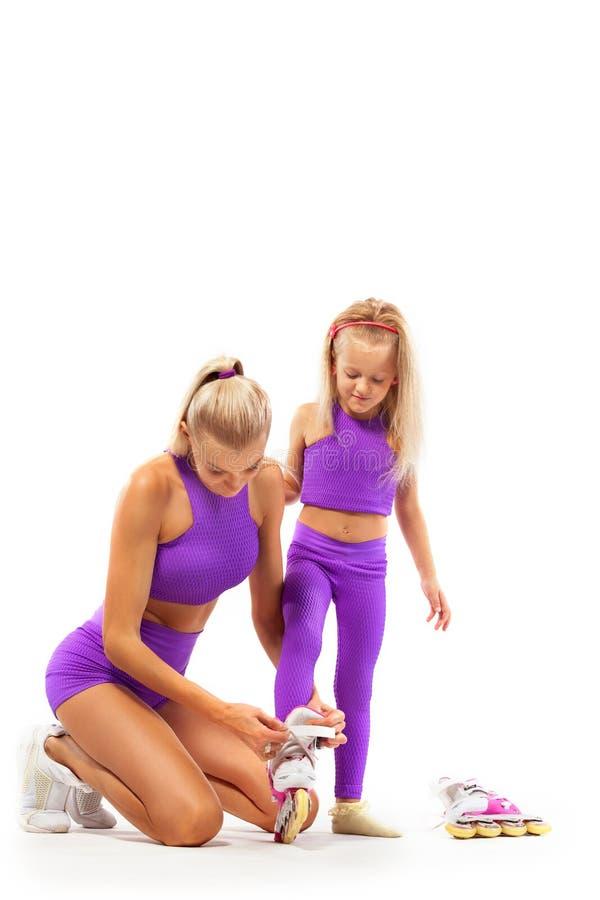 Familia, madre e hija, presentando en el estudio que lleva rollerskates en línea fotos de archivo
