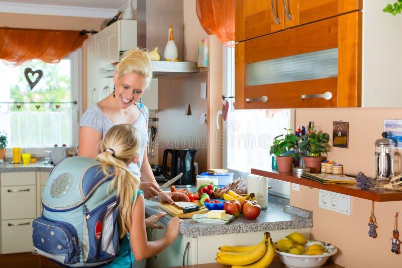 Familia - madre que hace el desayuno para la escuela imágenes de archivo libres de regalías