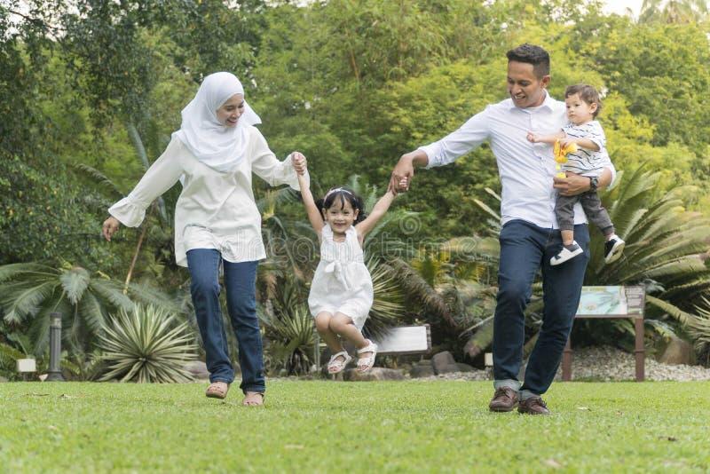 Familia malaya en el parque recreativo que se divierte fotos de archivo