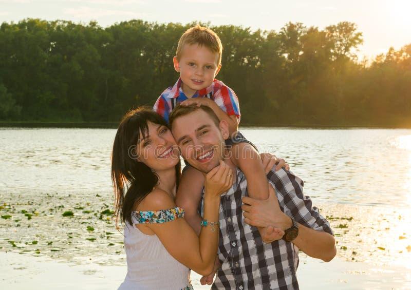 Familia, mamá, papá e hijo felices cerca del río en los rayos del sol fotos de archivo