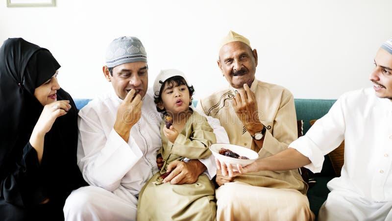 Familia medio-oriental que come fechas juntas imagenes de archivo